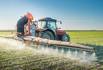 Photo of a tractor spraying a farm field