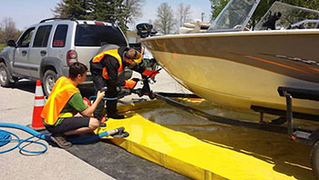 Photo of two provincial staff members in Selkirk, Manitoba, decontaminating the underside of a boat by spraying it with water at 60 degrees Celsius