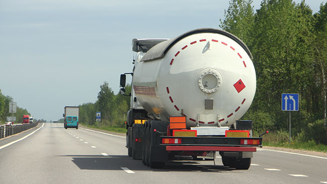 Photograph of a tanker truck being driven down a triple-lane highway