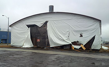 Exterior photo of Hangar 13, wrapped in vinyl tarps, at Canadian Forces Base Borden, Ontario