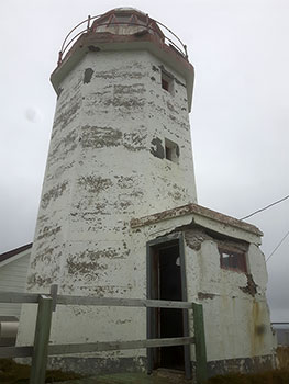 Exterior photo of the Green Island Lighthouse, and its damaged exterior, in Catalina, Newfoundland and Labrador